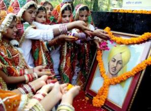 Children pay floral tribute to a portrait of Bhagat Singh  (Photo: IANS)