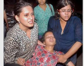An injured RCM girl student being carried away by friends