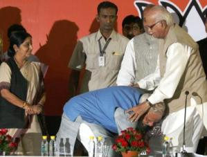 BJP Prime Ministerial candidate Narendra Modi touches the feet of party veteran L K Advani during a press conference in New Delhi on May 17, 2014. Party leader Sushma Swaraj also seen. (Photo: IANS)