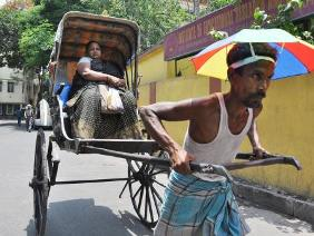 A rickshaw puller with an umbrella on a hot day in Kolkata on June 10, 2014. (Photo: Kuntal Chakrabarty/IANS)