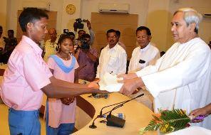 CM presenting dictionaries to Bonda students (pic-Biswaranjan Mishra)