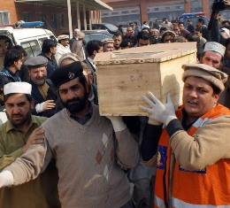 Pakistani volunteers move the coffin of a student from a hospital