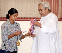 Srabani Nnada showing the medals she won recently to Chief Minister Naveen Patnaik on Wednesday