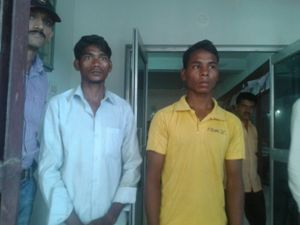 Niranjan Meleka (in white shirt) and Melesi Miniaka, who were detained by the police today for killing two persons on suspicion of practicing sorcery