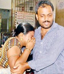 A man tries to console his grieving wife who lost her baby at the Sishu Bhavan in Cuttack