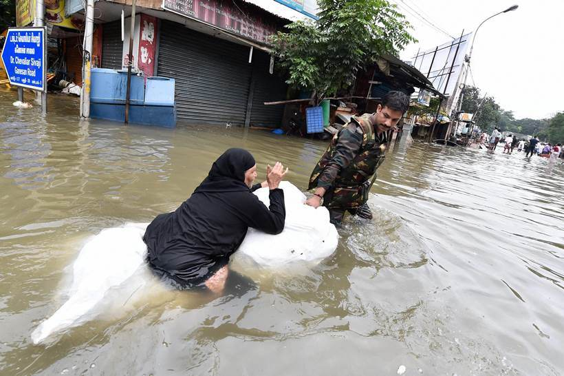 Chennai: Army personnel rescuing woman from a flooded locality in rain-hit Chennai on Thursday. Pic Courtesy: indianexpress.com