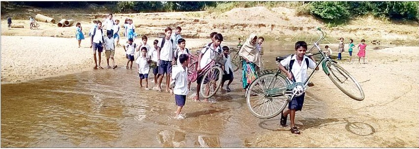 students wading through river