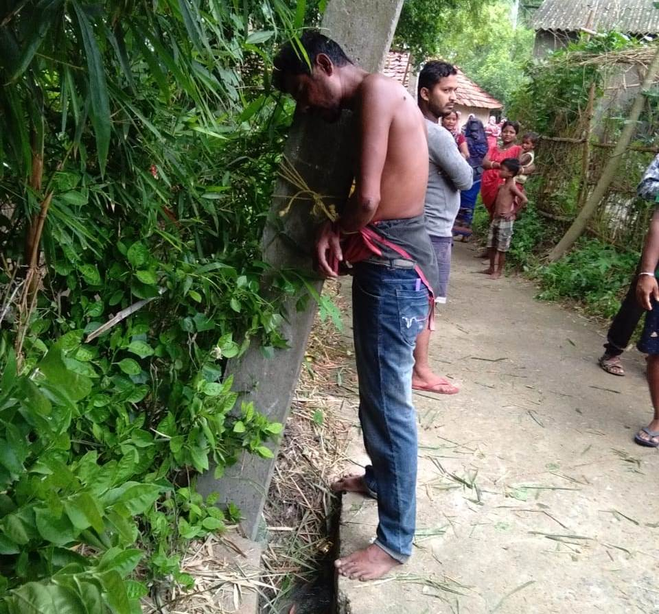 man tied to pole