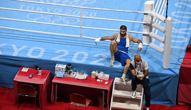 French boxer disqualified for headbutt, sits on ringside in protest.